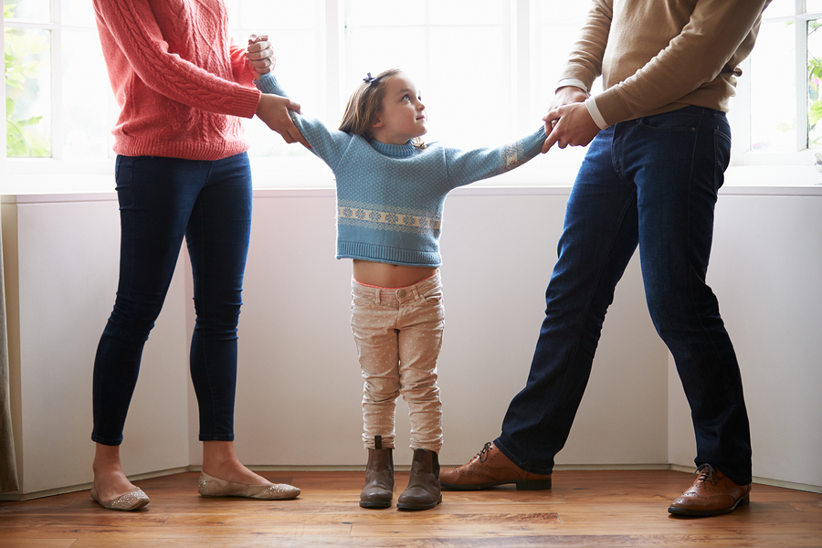 Parents pulling on arms of their child, symbolic of a relationship separation or divorce