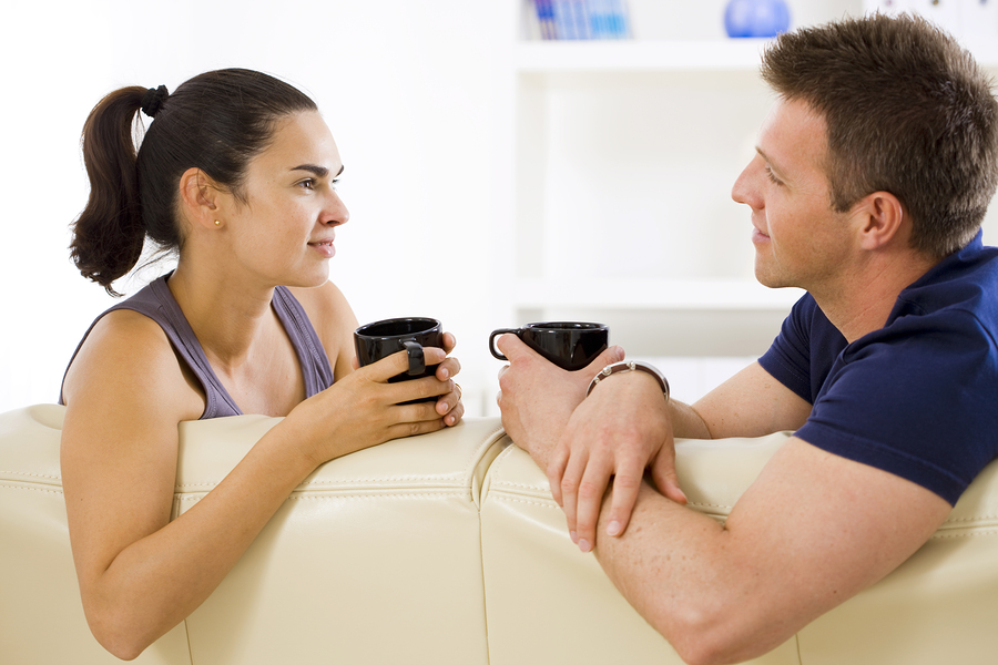 Man and woman talking on couch, holding coffee mugs