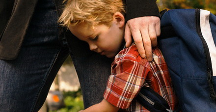 Son clinging to father's leg